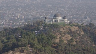 AX43_011 - 4K stock footage aerial video flying low over palm trees to approach and flyby the Griffith Observatory, Los Angeles California