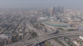 AX43_021 - 4K stock footage aerial video orbiting heavy traffic in the 110/10 interchange, and tilt to reveal the Los Angeles Convention Center and skyscrapers, Downtown Los Angeles, California