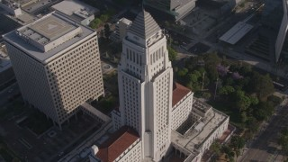 AX43_025 - 4K stock footage aerial video orbiting Los Angeles City Hall, Downtown Los Angeles, California