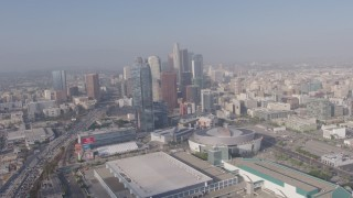 AX43_034 - 4K stock footage aerial video tilting from heavy rush hour traffic on I-110 to reveal Staples Center, Ritz-Carlton and Downtown Los Angeles skyscrapers in California