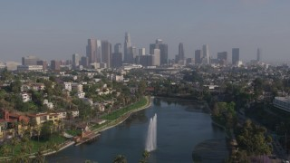 AX43_043 - 4K stock footage aerial video flying over Echo Park Lake fountain to approach Downtown Los Angeles skyline, California