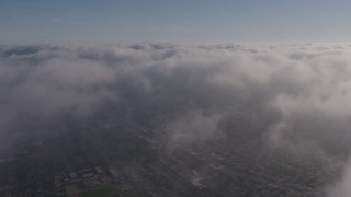 AX43_047 - 4K stock footage aerial video flying over a dense marine layer over Los Angeles, California