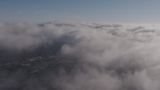 AX43_048 - 4K stock footage aerial video flying above marine layer with occasional breaks in the clouds, Los Angeles, California