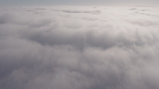 AX43_050 - 4K stock footage aerial video flying over a dense marine layer over Los Angeles, California and pan across the clouds