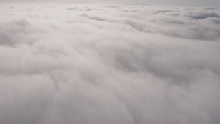 AX43_051 - 4K stock footage aerial video flying by a dense, sunlit marine layer, Los Angeles, California