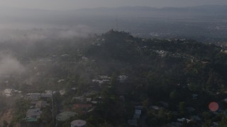 AX43_059 - 4K stock footage aerial video flying over marine layer to approach upscale, hillside homes near a radio tower, Beverly Hills, California