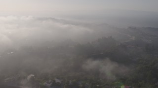 AX43_060 - 4K stock footage aerial video approaching the marine layer rolling over upscale, hillside homes in Beverly Hills, California