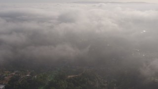 AX43_061 - 4K stock footage aerial video flying by hazy marine layer rolling over Beverly Hills, California