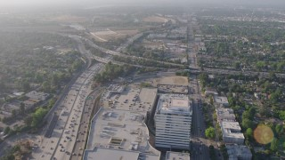 AX43_063 - 4K stock footage aerial video flying over office buildings and the Sherman Oaks Galleria to approach heavy traffic on the I-405 and 101 interchange, Sherman Oaks, California