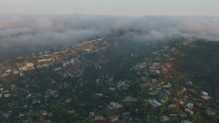 AX44_002 - 4K stock footage aerial video flying by upscale, hillside homes with fog rolling over the hills, Sherman Oaks, California, sunset