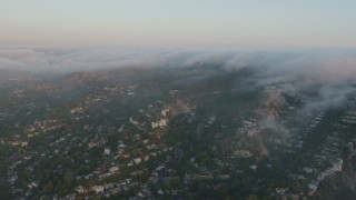 AX44_004 - 4K stock footage aerial video of Hillside homes with fog rolling over the tops of hills, Sherman Oaks, California, sunset