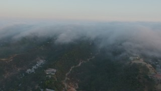 AX44_005 - 4K stock footage aerial video of fog rolling in over the hills in Sherman Oaks, California, sunset