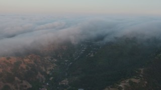 AX44_006 - 4K stock footage aerial video of a marine layer pouring over the hills, Studio City, California, sunset