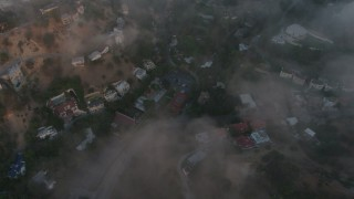 AX44_007 - 4K stock footage aerial video flying over homes with a marine layer, Studio City, California