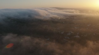 AX44_009 - 4K stock footage aerial video flying over marine layer above the hills, Studio City, California, sunset