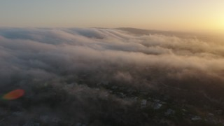 AX44_011 - 4K stock footage aerial video flying over marine layers above the hills, Studio City, California, sunset