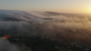 AX44_012 - 4K stock footage aerial video flying over marine layer above the hills, Studio City, California, sunset