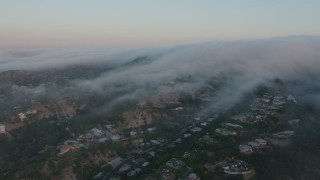 AX44_013 - 4K stock footage aerial video of a marine layer rolling over the hills and homes, Studio City, California, sunset