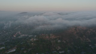 AX44_014 - 4K stock footage aerial video flying over homes with marine layer flowing over hills, Studio City, California, sunset