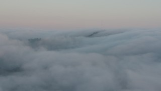 AX44_015 - 4K stock footage aerial video of radio tower peaking through a marine layer, Hollywood Hills, California, sunset