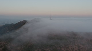 AX44_021 - 4K stock footage aerial video of the marine layer rolling over Hollywood Hills toward radio tower, California, sunset