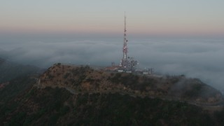 AX44_022 - 4K stock footage aerial video of a radio tower atop Hollywood Hills near marine layer, California, sunset