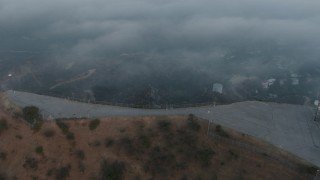 AX44_023 - 4K stock footage aerial video orbiting Hollywood Sign and radio tower cloaked in Marine Layer, California, sunset