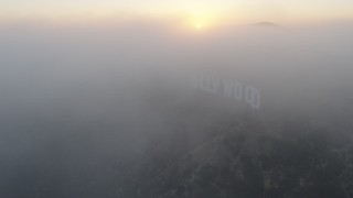 AX44_024 - 4K stock footage aerial video of Hollywood sign covered in thick marine layer, Los Angeles, California, sunset
