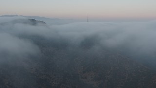 AX44_026 - 4K stock footage aerial video approaching radio tower peeking through marine layer, Hollywood Hills, California, sunset