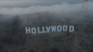 AX44_027 - 4K stock footage aerial video flying through marine layer revealing Hollywood Sign, California, sunset