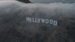 AX44_028 - 4K stock footage aerial video orbiting Hollywood Sign covered in marine layer, California, sunset
