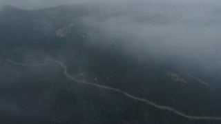 AX44_029 - 4K stock footage aerial video of winding roads in fog, Hollywood Hills, California, sunset