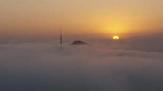 AX44_031 - 4K stock footage aerial video of the sunset behind Hollywood Hills, radio tower covered in Marine Layer, California