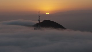 AX44_032 - 4K stock footage aerial video of sun setting behind Hollywood Hills and radio tower in marine layer, California