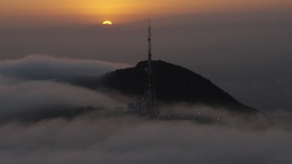 AX44_033 - 4K stock footage aerial video approaching radio tower atop a hill in marine layer, Hollywood Hills, California, sunset