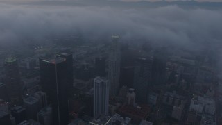 AX44_043 - 4K stock footage aerial video of a city covered in marine layer, Downtown Los Angeles, sunset