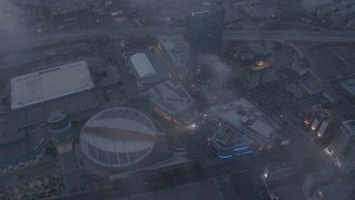 AX44_044 - 4K stock footage aerial video of Staples Center and Nokia Theater below marine layer, Downtown Los Angeles, twilight