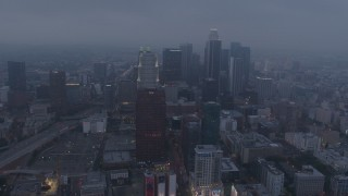AX44_047 - 4K stock footage aerial video of skyscrapers through marine layer, Downtown Los Angeles, twilight