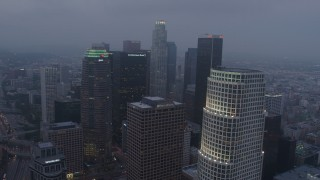 AX44_049 - 4K stock footage aerial video flying by skyscrapers, Downtown Los Angeles, twilight