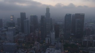 AX44_051 - 4K stock footage aerial video of a marine layer hanging over skyscrapers, Downtown Los Angeles, twilight