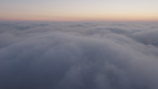 AX44_055 - 4K stock footage aerial video flying over marine layer, Los Angeles twilight