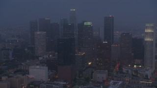 AX44_057 - 4K stock footage aerial video approaching city through marine layer, Downtown Los Angeles, night
