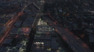 AX44_061 - 4K stock footage aerial video flying over light traffic on an interstate, Los Angeles, night