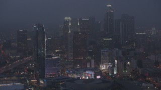 AX44_062 - 4K stock footage aerial video tilting up from the interstates revealing Downtown skyline, Los Angeles, night
