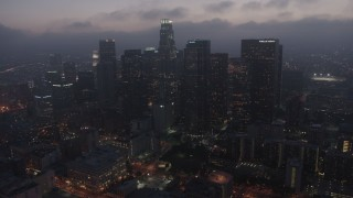AX44_068 - 4K stock footage aerial video approaching Downtown Los Angeles skyline below marine layer, night