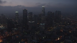 AX44_070 - 4K stock footage aerial video flying by skyscrapers below marine layer, Downtown Los Angeles, night