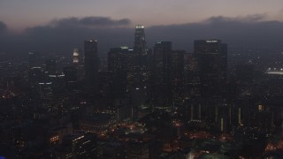 AX44_073 - 4K stock footage aerial video flying by skyscrapers below marine layer, Downtown Los Angeles, sunset