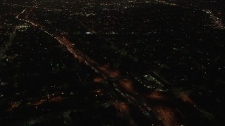 AX44_087 - 4K stock footage aerial video orbiting a highway with medium traffic among city light, Echo Park, Los Angeles, night