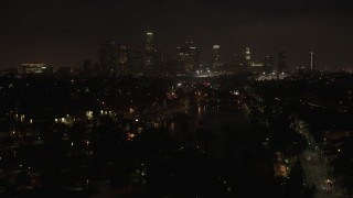 AX44_088 - 4K stock footage aerial video approaching skyline, Downtown Los Angeles, night