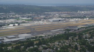 AX45_007 - 5K stock footage aerial video flying by Boeing Field with a row of commercial planes on the other side of the runways, Seattle, Washington